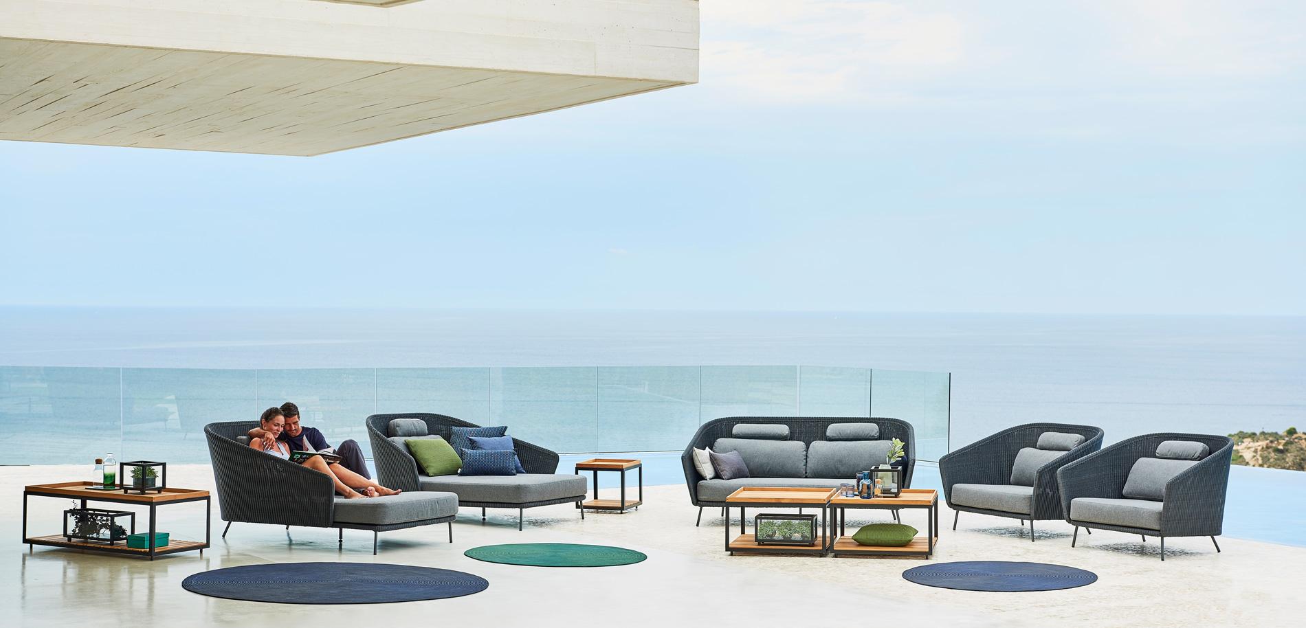 Verschiedene Objekte aus der Accessoires-Kollektion von Cane-line, darunter Teppiche und Beistelltische, zusammen mit Möbeln der Serie Mega.