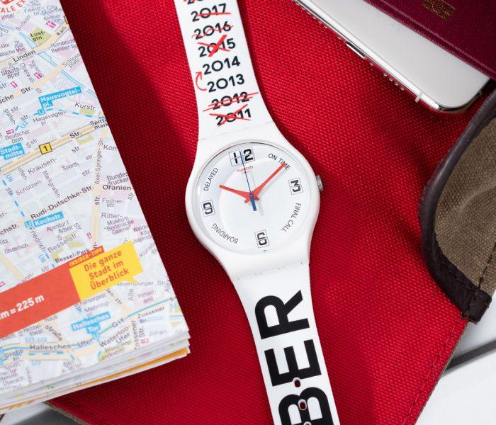 Das neue Sondermodell Swatch Delayed macht sich über die neun Jahre verspätete Eröffnung des Flughafens Berlin Brandenburg auf originelle Weise lustig.