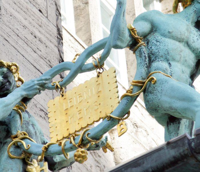 """Der Leibniz-Keks ist die Ikone unter den Kleingebäcken und eine Lösung für ein Problem, mit dem sich bereits Gottfried Wilhelm Leibniz beschäftigt hat. Unser Titelbild zeigt die 1910 geschaffenen Brezelmännner mit dem """"goldenen Keks"""", welche die Bahlsen-Firmenzentrale in Hannover zieren."""